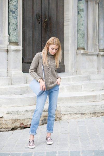 grå, grovstickad tröja med ljusblå slim fit jeans med muddar