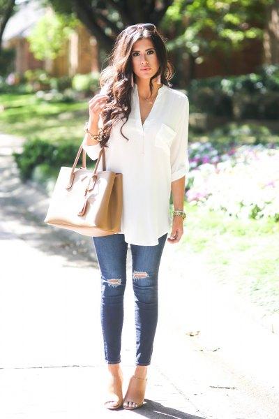vit, elegant tunikatopp med knappar och blå ribbade skinny jeans