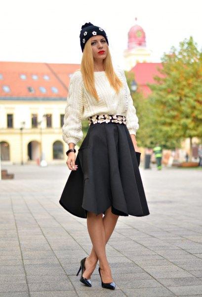 vit, grovstickad tröja med svart veckad kjol och klackar