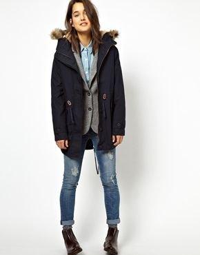 Parkacover med mörkblå päls, grå väst och jeans