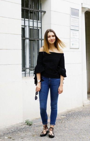 svart off-the-shoulder blus med halva ärmar och blå skinny jeans