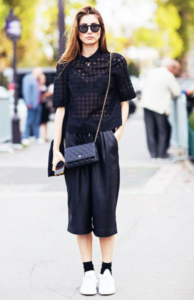 svart, halvtransparent kortärmad blus med skurna byxor med breda ben i läder