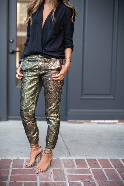 svart blus med V-ringning och smala byxor i paljetterat guld