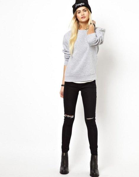 grå tröja med rippade svarta skinny jeans och stickad hatt