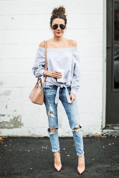 ljusblå knuten från axelblusen med kraftigt sönderrivna jeans