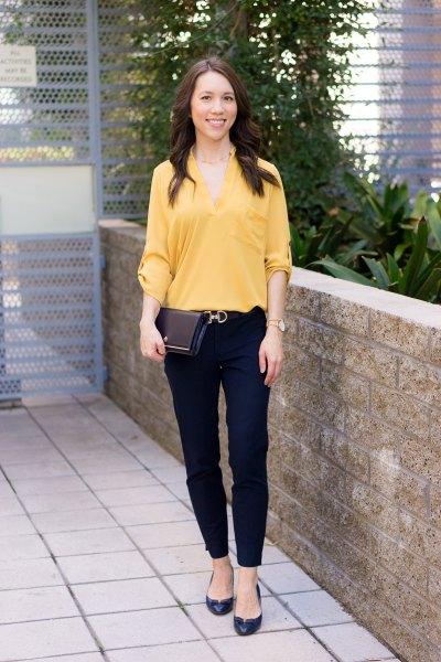 gul blus med V-ringning med svarta chinos och lägenheter