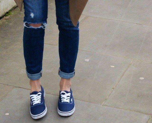 Mörkblå skinny jeans med en brun parkajacka och mörkblå sneakers