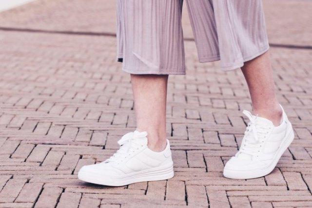 grå randiga byxor i chiffong med vida ben och vita sneakers