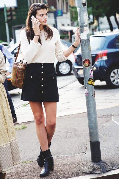 vit ribbad tröja med svart minikjol med knapplås och fotkängor