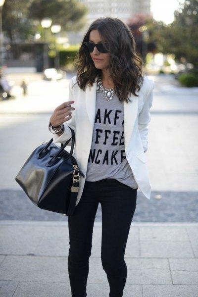 grå meddelande-t-shirt med vit kavajjacka och svarta skinny jeans