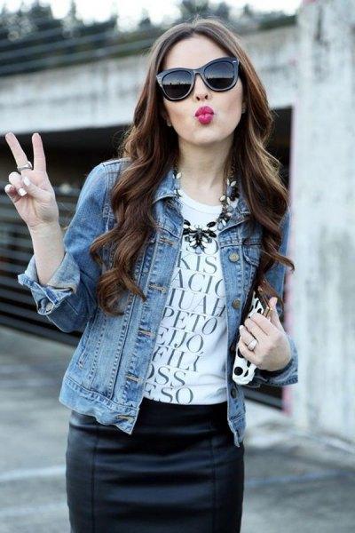 blå jeansjacka med vit grafisk t-shirt och svart läder kjol