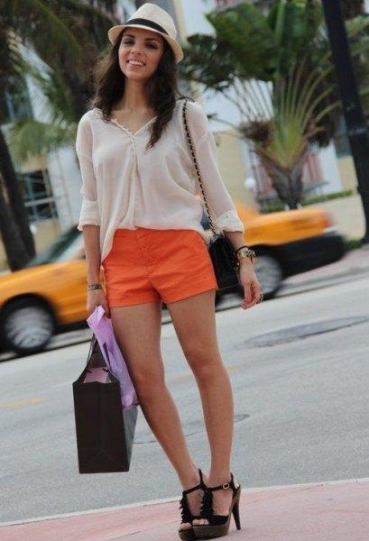vit blus med stråhatt och orange mini-shorts
