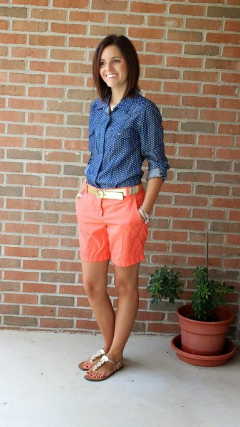 Skjorta med mörkblå och vita prickar och knappar med längre orange shorts