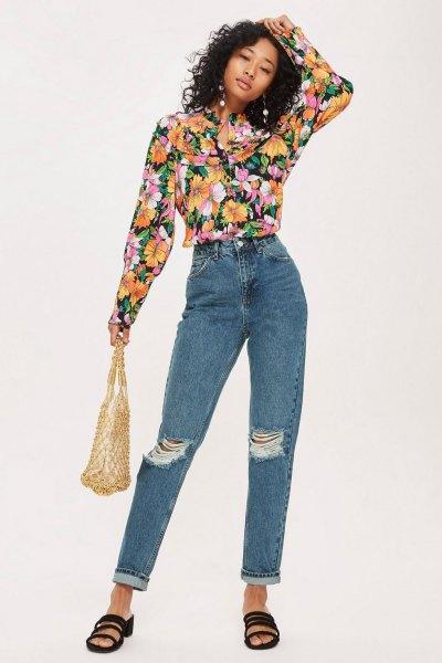 svart blus med blommönster och blå rippade jeans