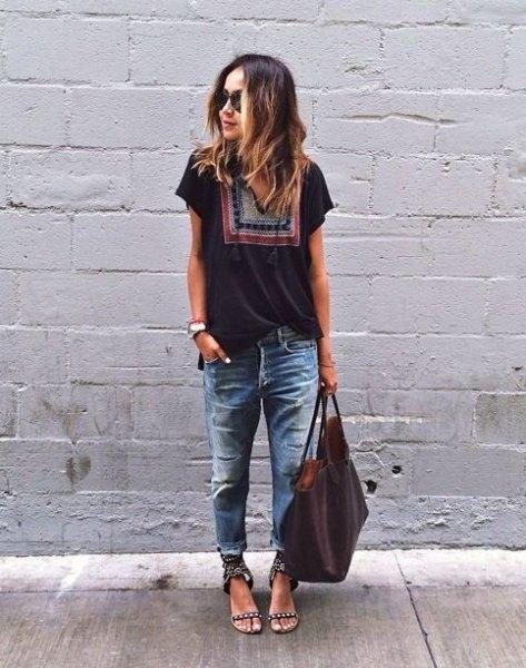 svart t-shirt med stamtryck med dåligt sönderrivna och tvättade pojkvänjeans