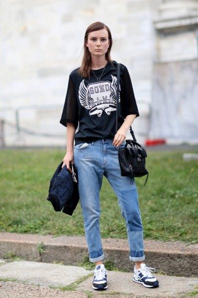 svart oversize-t-shirt med avslappnad blå jeans med muddar
