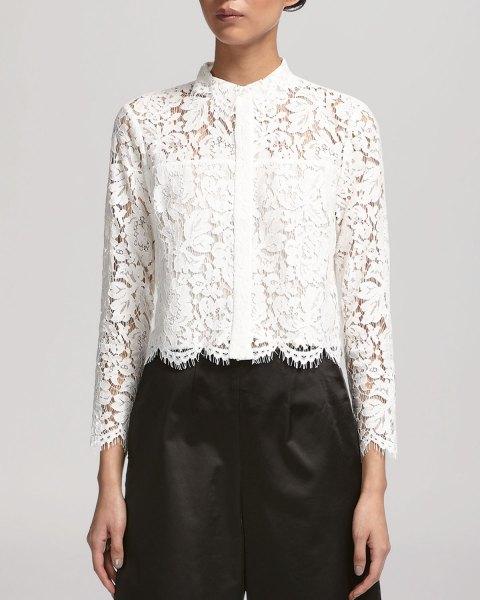 vit spetsskjorta med kantad fåll, svarta byxor