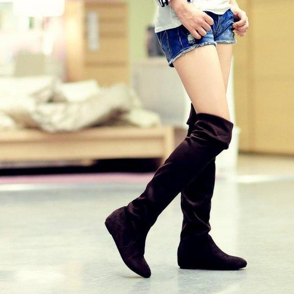 svarta knähöga stövlar över jeansshorts