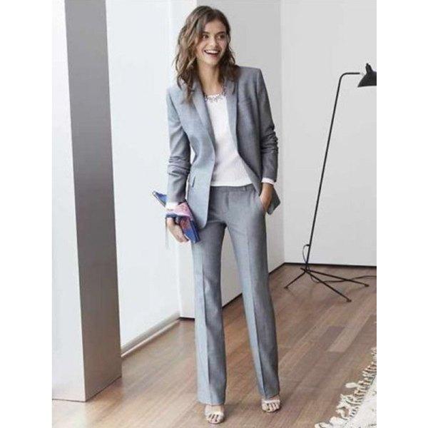 grå kostym med vit chiffongblus och uttalandekedja