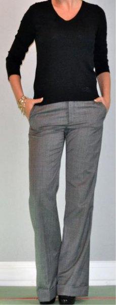 svart tröja med V-ringning och grå kostymbyxa med vida ben