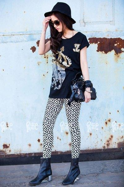 svart grafisk t-shirt med högklackade läderstövlar och filthatt