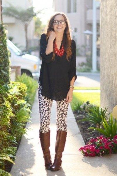 svart chiffongblus med knähöga läderstövlar och mönstrade leggings