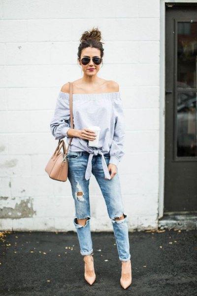 Ljusblå knuten från axelblusen med riktigt rippade jeans med muddar