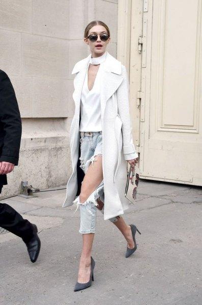 Vit longline-ullrock med en sidenblus med V-ringning och sönderrivna jeans
