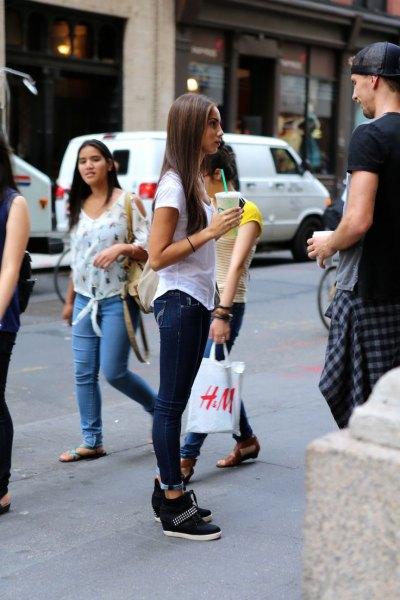 grå t-shirt med mörkblå skinny jeans och svarta sneakers med dolda kilar