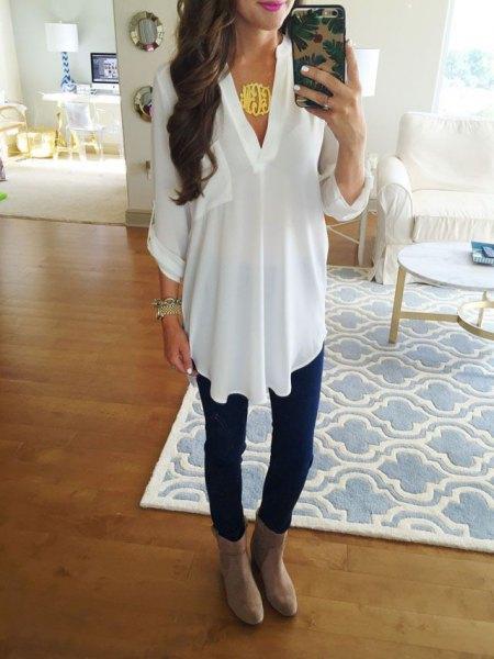 vit chiffong tunikatopp med mörkblå skinny jeans och läderstövlar