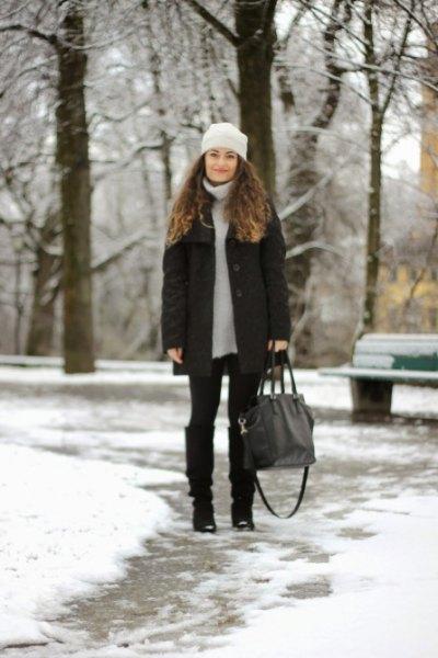 ljusgrå tröja klänning med dunjacka och svarta knähöga snöskor