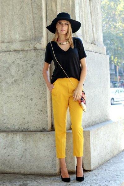 svart V-ringad T-shirt, floppy hatt och beskurna gula byxor