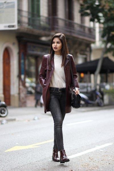 lång kastanjebrun läderjacka med vit tröja och grå jeans