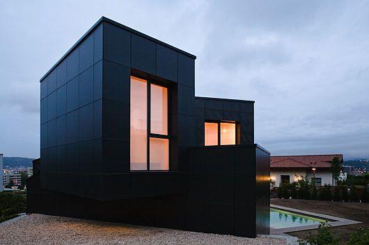 Enkel-exteriör-av-mystisk-modern-Q-hus-med-svart-vägg.jpg.