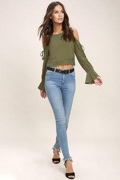 olivgrön långärmad topp med kall axel och ljusblå jeans