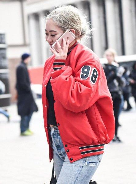 röd jacka med svart, kort T-shirt och blå skinny jeans