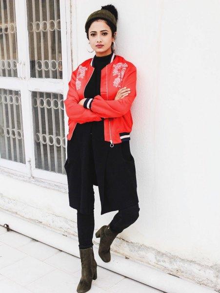 röd broderad bomberjacka med svart tröja med rund halsringning och smala jeans