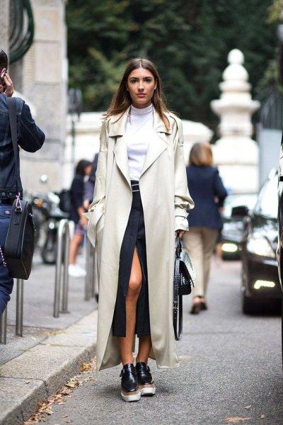 Elfenben maxi trenchcoat med vit tröja och svart hög split kjol
