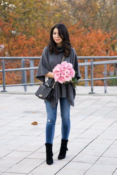 grå ponchotröja med blå skinny jeans och svarta stövlar