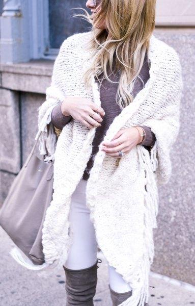 vit kabelstickad tröja med overknee stövlar