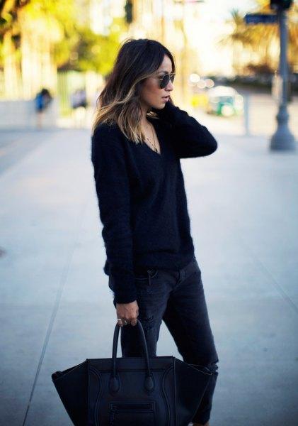 svart, grovstickad tröja med V-ringning och mörka smala jeans