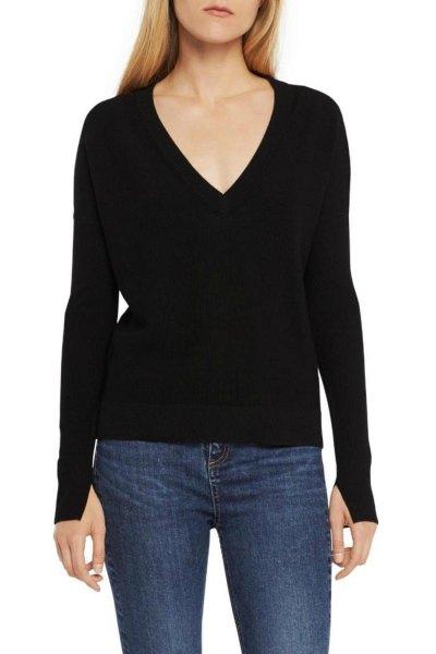 svart stickad tröja med djup V-ringning och mörkblå skinny jeans
