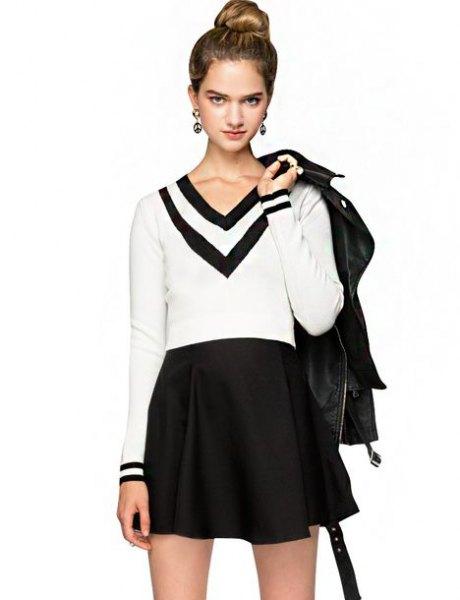 vit och svart tröja med V-ringning och miniraterad kjol med hög midja