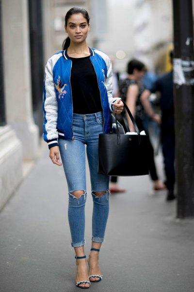 blå och vit broderad bomberjacka med svart t-shirt och rippade jeans