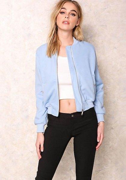 babyblå bomberjacka med vit, kort t-shirt och svarta jeans med smal passform