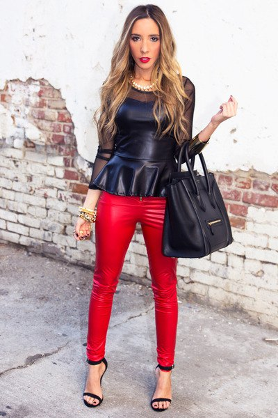svart peplum-topp i läder med matchande röda byxor