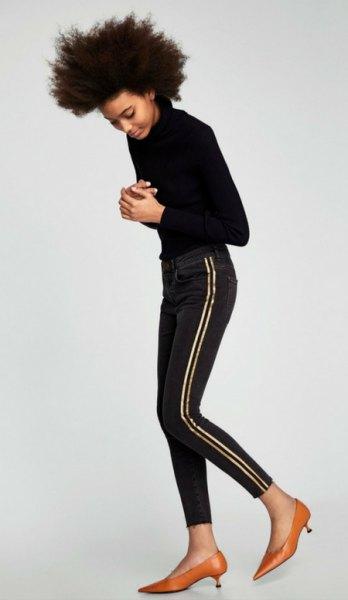 svart stickad tröja med smala jeans och guldkattunge klackar