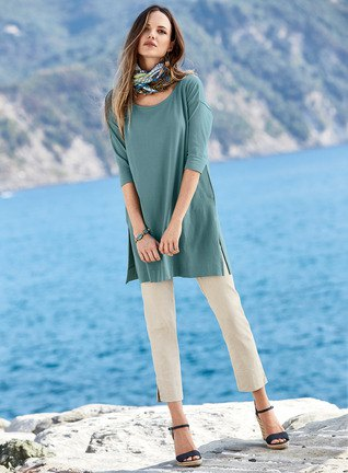 blågrön tunikatopp med halva ärmar och vita, beskurna byxor