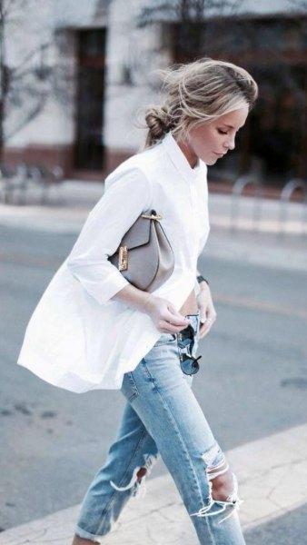 överdimensionerad vit skjorta med knappar och rippade ljusblå knä jeans