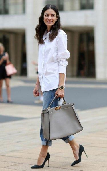 vit skjorta med knappar, blå pojkvänjeans med manschetter och rosa plånbok
